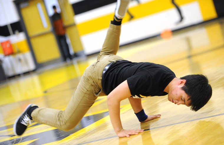 John Oh, 16, a junior and co-captain of the Mt. Hebron Break Dance team, performs a breaking move for the crowd at halftime of the Hebron vs. Centennial girls basketball game, Thursday, Feb. 19, 2015 in Ellicott City. (Jon Sham/BSMG)