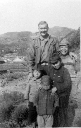 "Cpl. Len Pojunas Sr. in Japan with Japanese school children. The two older children wear Japanese military kepis. The child to the left is wearing Pojunas' Marine cap. As recalled by Pojunas Jr., ""the oldest schoolboy asked if my father had killed his mother (my grandmother) to become a Marine. That was the belief among the Japanese."""