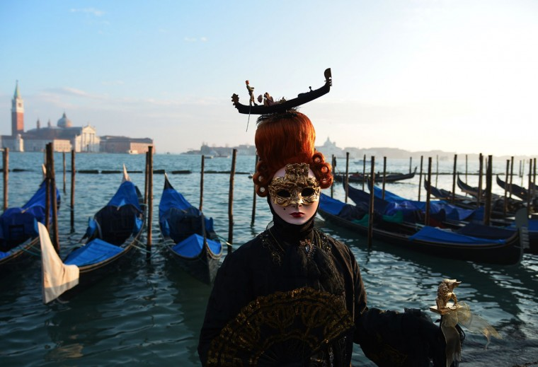 A costumed reveler poses in front of gondolas at St Mark's square (Piazza San marco) during the Venice Carnival on February 8, 2015 in Venice. (VINCENZO PINTO/AFP/Getty Images)