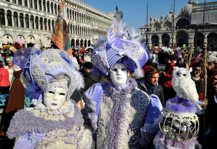 People wearing traditional costumes parade in St. Mark's square in Venice, Italy, Sunday, Feb. 8, 2015, on the occasion of the Venice Carnival. (AP Photo/Sebastiano Casellati)