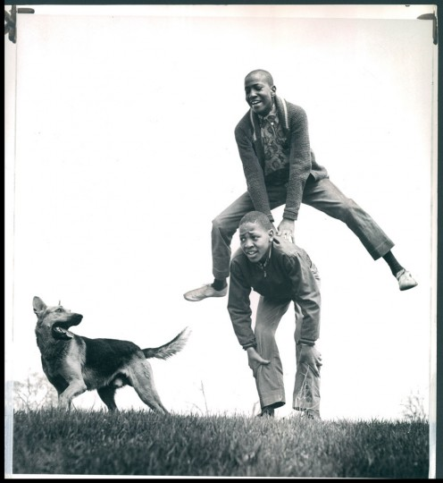 "April 19, 1962: The cold weather over, the mercury rose yesterday and Ralph Willett, 14, welcomed change by leap-frogging over Barrington Wood, 13, in Druid Hill Park as ""Duke"" runs along side. Photo by Ellis Malashuk"