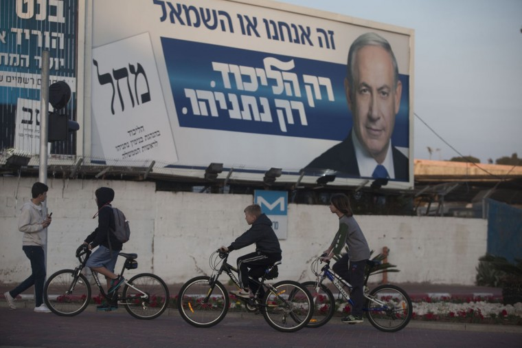 Israeli children ride bicycles past a billboard of Prime Minister Benjamin Netanyahu on election day on March 17, 2015 in Ramat Gan, Israel. Israel's general election voting has begun today as polls show on that Chairman of the Zionist Union party, Isaac Herzog stands as the only rival to current Prime Minister Benjamin Netanyahu. (Photo by Lior Mizrahi/Getty Images)