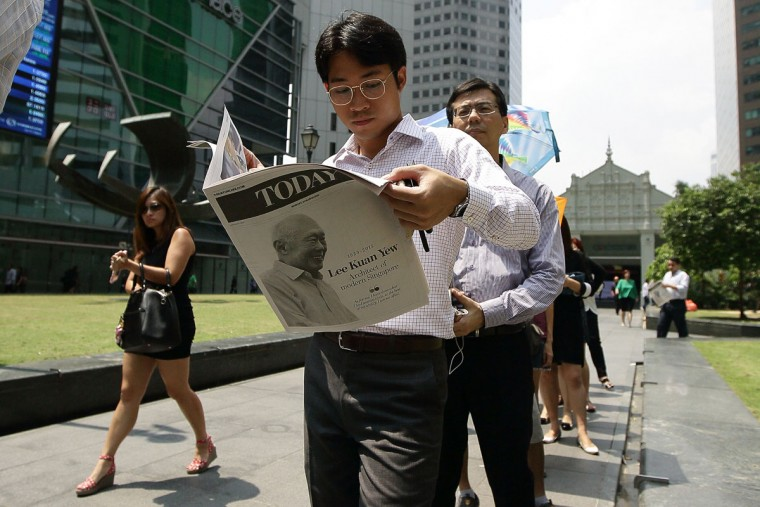 A man reads a free special edition newspaper at Raffles Place following the passing of former Prime Minister Lee Kuan Yew on March 23, 2015 in Singapore. Former Prime Minister, Lee Kuan Yew, 91, died last night at Singapore General Hospital after spending several weeks in critical condition after being admitted for pnemonia on February 5. Lee Kuan Yew served as the first Prime Minister of Singapore when it gained rule from Britain in 1959 and until he stepped down in 1990. (Photo by Suhaimi Abdullah/Getty Images)