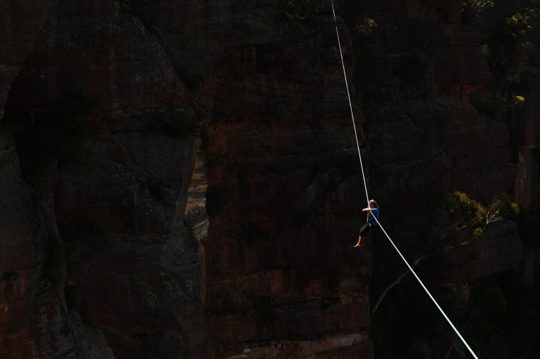 Joseph Huard of Canada relaxes on a 90m highline rigged between cliffs at Corroboree Walls in Mount Victoria on March 8, 2015 in the Blue Mountains, Australia. (Photo by Cameron Spencer/Getty Images)