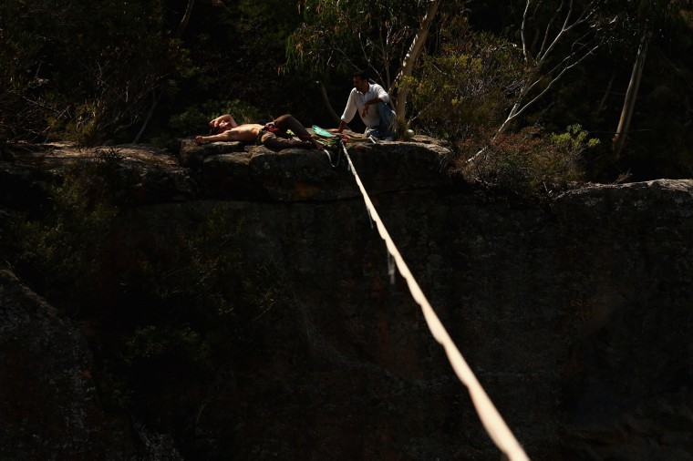 Guilherme Lopes of Brazil relaxes after successfully walking a 60m highline rigged between cliffs at Corroboree Walls in Mount Victoria on March 8, 2015 in the Blue Mountains, Australia. (Photo by Cameron Spencer/Getty Images)