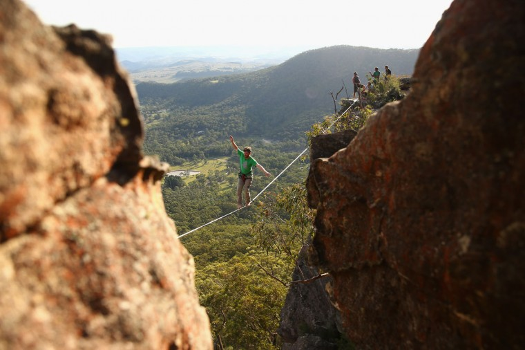Luke Sarantos of Australia balances on a highline rigged between cliffs at Corroboree Walls in Mount Victoria on March 7, 2015 in the Blue Mountains, Australia. (Photo by Cameron Spencer/Getty Images)