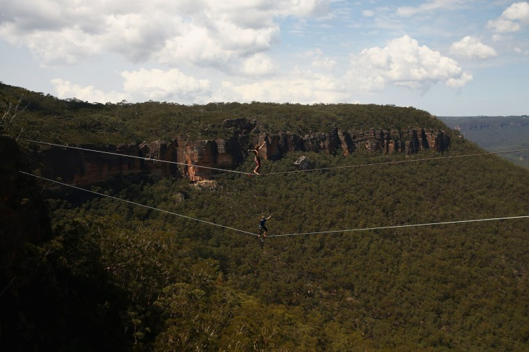 Travis Foster of the United States walks on a 60m highline (top) and Joseph Huard of Canada walks on a 90m highline (bottom) rigged between cliffs at Corroboree Walls in Mount Victoria on March 8, 2015 in the Blue Mountains, Australia. (Photo by Cameron Spencer/Getty Images)