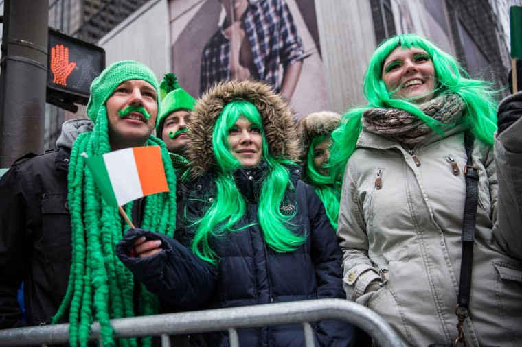 Revelers watch the annual St. Patrick's Day Parade along Fifth Ave in Manhattan on March 17, 2014 in New York City. Political controversy surrounded this year's parade, as New York City Mayor Bill De Blasio decided not to march due to the parade organizer's policy to ban participants that identify themselves as lesbian, gay, bisexual or transgender. Heineken and Guinness announced earlier that they would drop their sponsorship of the parade for along the same reasons. (Photo by Andrew Burton/Getty Images)
