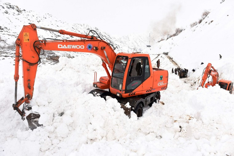 Afghan survivors of an avalanhce gather as excavators clear snow from a road near in the Abdullah Khil village of the Dara district of Panjshir province, north of Kabul on March 1, 2015. Afghan President Ashraf Ghani February 28 pledged to set up a relief fund for the victims of avalanches that claimed over 280 lives, and called for international help with the relief effort. (Shah Marai/AFP/Getty Images)