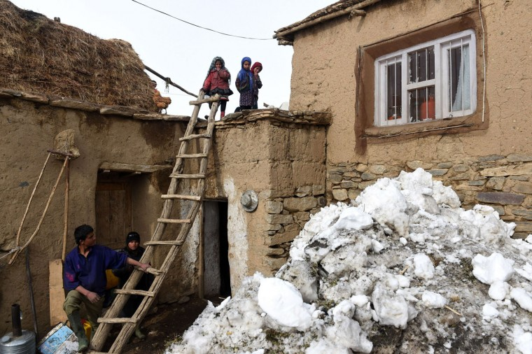 Afghan survivors of an avalanche stand on rooftop of their house in the Abdullah Khil village of the Dara district of Panjshir province, north of Kabul on March 1, 2015. Afghan President Ashraf Ghani February 28 pledged to set up a relief fund for the victims of avalanches that claimed over 280 lives, and called for international help with the relief effort. (Shah Marai/AFP/Getty Images)