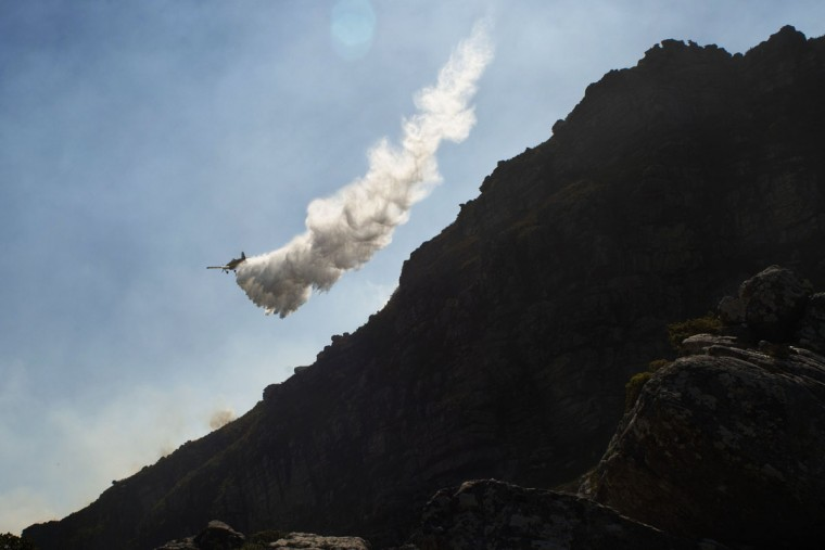 A firefighting aircraft dumps water on a part of a large bush fire raging in the mountains on the Cape Peninsula on March 2, 2015. (RODGER BOSCH/AFP/Getty Images)