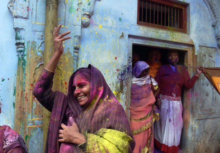 "An Indian widow dances as she celebrates Holi or ""festival of colors"" in Vrindavan on March 3, 2015. Widows congregated on a small patio of the ashram in which they live and danced and played with colored powder to celebrate the occasion. The widows of this and other ashrams in this northern town are sponsored by the NGO, Sulabh International which funds most of their needs. Shunned from society when their husbands die, not for religious reasons, but because of tradition, many Indian widows have been otracized from society and no longer live with their families and are forced to beg for food. Almost 2,000 of the estimated 34 million widows currently living in India live in Vrindavan and benefit from the welfare extended by the NGO. (Roberto Schmidt/AFP/Getty Images)"