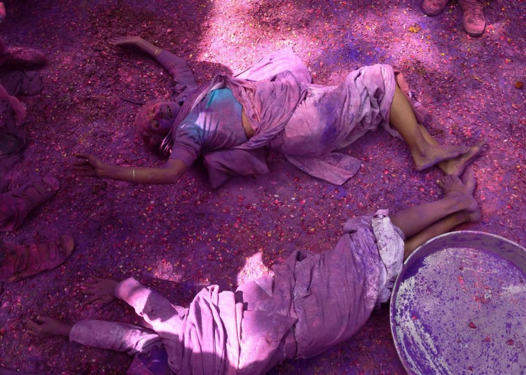 """Two Indian widows roll on a patio floor covered in flower petals and colored powder as they celebrate Holi or """"festival of colors"""" in Vrindavan on March 3, 2015. Widows congregated on a small patio of the ashram in which they live and danced and played with colored powder to celebrate the occasion. The widows of this and other ashrams in this northern town are sponsored by the NGO, Sulabh International which funds most of their needs. Shunned from society when their husbands die, not for religious reasons, but because of tradition, many Indian widows have been otracized from society and no longer live with their families and are forced to beg for food. Almost 2,000 of the estimated 34 million widows currently living in India live in Vrindavan and benefit from the welfare extended by the NGO. (Roberto Schmidt/AFP/Getty Images)"""