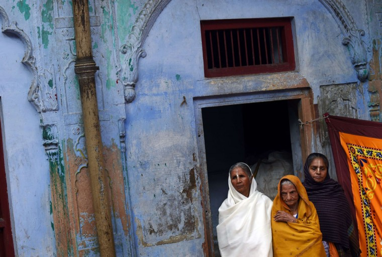 """Indian widows listen to a talk by Bindeshwar Pathak, founder of NGO Sulabh International which funds some Indian widows sheltering in ashrams in Vindravan on March 3, 2015. Shunned from society when their husbands die, not for religious reasons, but because of tradition many Indian widows were otracized from society, no longer lived with their families and were forced to beg for food. Almost 2,000 of the estimated 34 million widows currently living in India live in Vrindavan and benefit from the welfare extended by the NGO. The widows were attending a ceremony where they celebrate Holi or """"festival of colors"""". (Roberto Schmidt/AFP/Getty Images)"""