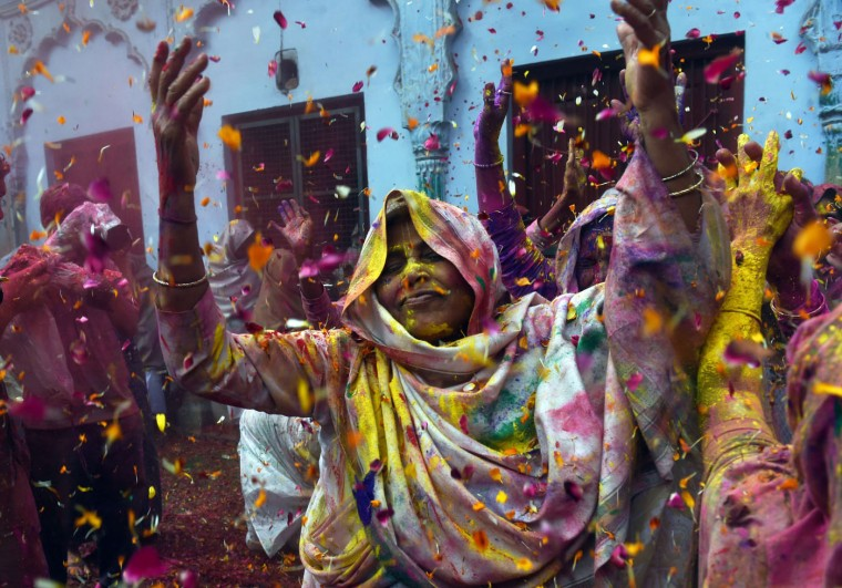 "Indian widows dance as they celebrate Holi or ""festival of colors"" in Vrindavan on March 3, 2015. Widows congregated on a small patio of the ashram in which they live and danced and played with colored powder to celebrate the occasion. The widows of this and other ashrams in this northern town are sponsored by the NGO, Sulabh International which funds most of their needs. Shunned from society when their husbands die, not for religious reasons, but because of tradition, many Indian widows have been otracized from society and no longer live with their families and are forced to beg for food. Almost 2,000 of the estimated 34 million widows currently living in India live in Vrindavan and benefit from the welfare extended by the NGO. (Roberto Schmidt/AFP/Getty Images)"