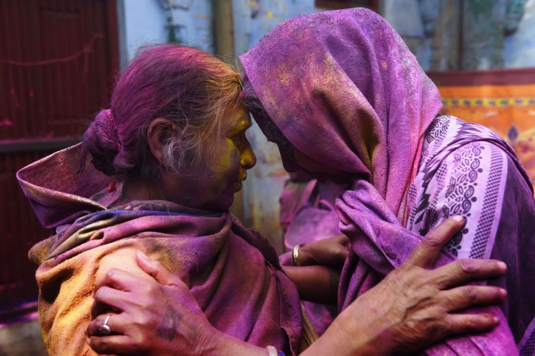"Two Indian widows touch their foreheads as they celebrate Holi or ""festival of colors"" in Vrindavan on March 3, 2015. Widows congregated on a small patio of the ashram in which they live and danced and played with colored powder to celebrate the occasion. The widows of this and other ashrams in this northern town are sponsored by the NGO, Sulabh International which funds most of their needs. Shunned from society when their husbands die, not for religious reasons, but because of tradition, many Indian widows have been otracized from society and no longer live with their families and are forced to beg for food. Almost 2,000 of the estimated 34 million widows currently living in India live in Vrindavan and benefit from the welfare extended by the NGO. (Roberto Schmidt/AFP/Getty Images)"