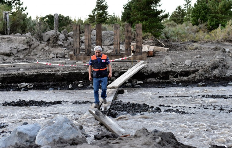 An employee of the National Office of Emergency of the Interior Ministry crosses the Turbio river after its bridge was destroyed by stones and volcanic material of the Villarrica volcano in Pucon, some 800 km south of Santiago, on March 5, 2015. The Villarrica erupted early Tuesday, spewing fiery plumes of lava into the night sky and forcing the evacuation of some 3,600 people in nearby towns. In its first major eruption in 15 years, the Villarrica volcano, prompted authorities to declare a red alert, the National Emergency Office said. Chile keeps the red alert two days after the Villarrica volcano erupted but reduced the risk area from 10 to 5 km. (Martin Bernetti/AFP/Getty Images)