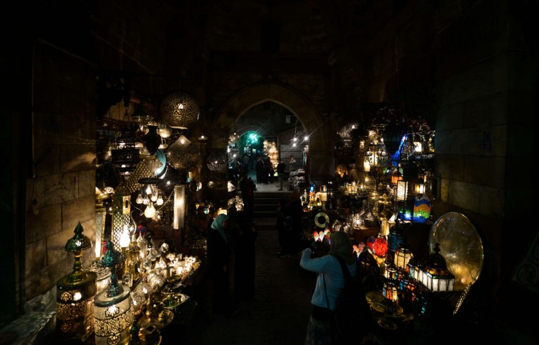 People walk past shops in al-Moez street in Cairos Khan el-Khalili district, in Egypt on March 7, 2015. Al-Moez street is one of the oldest streets in Cairo, approximately one kilometer long, and according to a United Nations study it's found to have the greatest concentration of medieval architectural treasures in the Islamic world. (AFP Photo/Mohamed El-shahed)