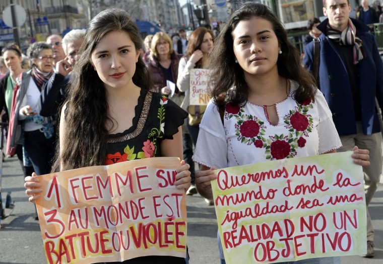 "Women hold signs reading in French ""One out of three women is beaten or raped"" and in Spanish ""We want a world where equality is a reality and not an objective"" as they take part in a parade marking International Women's Day in Paris on March 8, 2015. (Loic Venance/AFP/Getty Images)"