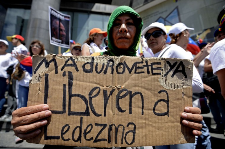 An opponent of the government of Venezuelan President Nicolas Maduro takes part in a march in Caracas to mark International Women's Day on March 8, 2015. Late president Hugo Chavez's hand-picked successor, Maduro, is struggling to revive the recession-hit economy and address chronic shortages of basic goods. Maduro has taken a harder line than Chavez, jailing opponents and allowing the security forces to use deadly force to control public demonstrations. His approval rating is now hovering around 20 percent, putting the Chavistas at risk of losing key legislative elections later this year. (Federico Parra/AFP/Getty Images)