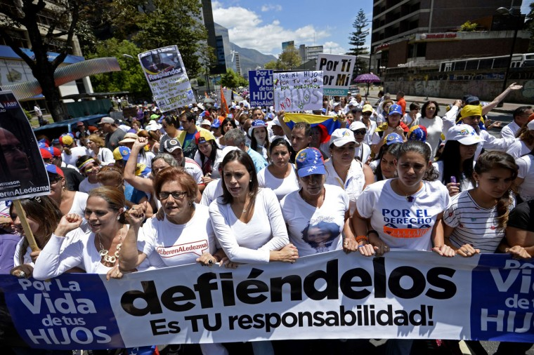 Venezuelan opposition leader Maria Corina Machado (C) joins thousands of opponents of the government of President Nicolas Maduro in a march in Caracas to mark International Women's Day on March 8, 2015. Late president Hugo Chavez's hand-picked successor, Maduro, is struggling to revive the recession-hit economy and address chronic shortages of basic goods. Maduro has taken a harder line than Chavez, jailing opponents and allowing the security forces to use deadly force to control public demonstrations. His approval rating is now hovering around 20 percent, putting the Chavistas at risk of losing key legislative elections later this year. (Federico Parra/AFP/Getty Images)