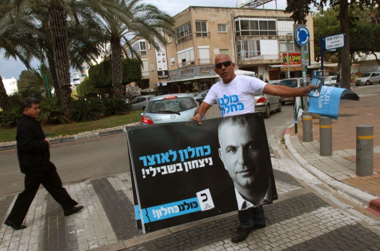 A supporter of Israeli politician, a popular former Likud minister and head the Kulanu party, Moshe Kahlon (portrait) distributes campaign material as Kahlon visits the Israeli city of Hadera on March 13, 2015, ahead of the March 17 general elections. (Gil Cohen-Magen/AFP/Getty Images)