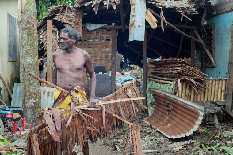 """This handout photo taken and received on March 15, 2015 by UNICEF Pacific shows a resident picking up debris outside his home after it was badly damaged by Cyclone Pam, outside the Vanuatu capital of Port Vila. Cyclone-devastated Vanuatu declared a state of emergency on March 15 as relief agencies scrambled to get help to the remote Pacific nation amid reports entire villages were """"blown away"""" when the monster storm swept through. (UNICEF Pacific/AFP/Getty Images)"""