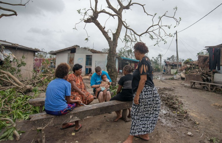 """This handout photo taken and received on March 15, 2015 by UNICEF Pacific shows a UNICEF worker (C-in blue top) feeding a child as residents sit among debris caused by Cyclone Pam, outside the Vanuatu capital of Port Vila. Cyclone-devastated Vanuatu declared a state of emergency on March 15 as relief agencies scrambled to get help to the remote Pacific nation amid reports entire villages were """"blown away"""" when the monster storm swept through. (UNICEF Pacific/AFP/Getty Images)"""