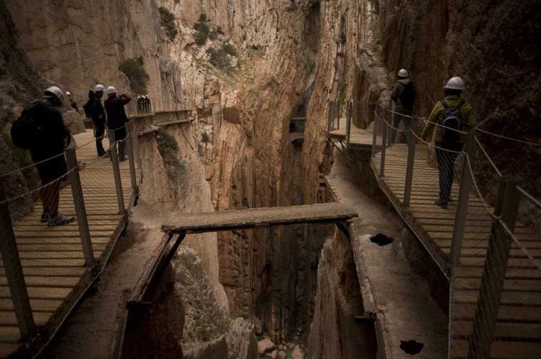 "Journalists and visitors walk during a visit to the foot-path ""El Caminito del Rey"" (King's little path) a narrow walkway hanging and carved on the steep walls of a defile in Ardales near Malaga on March 15, 2015. (Jorge Guerrero/AFP/Getty Images)"