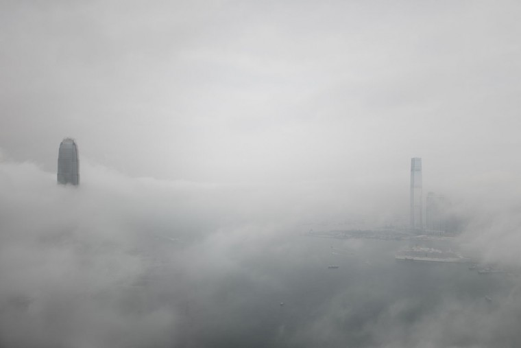 The IFC (L) and ICC (R) towers are seen shrouded in fog in Hong Kong on March 16, 2015. The foggy weather in the Southern Chinese city is caused by a humid maritime airstream affecting the south China coastal areas. (AFP Photo/Philippe Lopez)