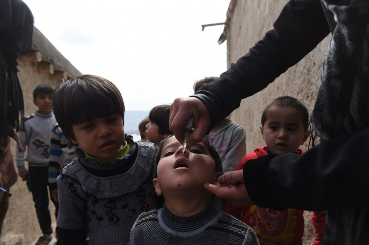 An Afghan health worker administers polio vaccine drops to a child on the second day of a vaccination campaign in Kabul on March 16, 2015. Nearly nine million children throughout Afghanistan will be immunized during a three-day national polio immunization drive launched on March 15.The immunization campaign comes shortly after Afghanistan reported its first case of polio virus for 2015, in Helmand, in the Southern Region. Afghanistan and Pakistan are the only two countries in the world to have reported cases of the crippling polio virus in the past eight months and it is increasingly likely that these are the last two countries on Earth with active polio transmission. (AFP Photo/Shah Marai)