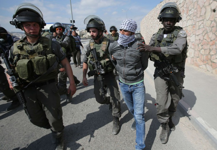 A Palestinian man is detained by members of the Israeli security forces during clashes following a march attended by Palestinian, Israeli and foreign demonstrators, to send a message to Israeli politicians as people vote in the general elections, against what the Palestinians say is land confiscation by Israel for the building of Jewish settlements, near the West Bank town of Abu Dis on March 17, 2015. (Abbas Momani/AFP/Getty Images)