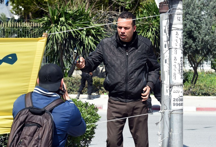 An armed Tunisian policeman (R) in plainclothes stops a photographer as security forces secure the area after gunmen attacked Tunis' famed Bardo Museum on March 18, 2015. At least seven foreigners and a Tunisian were killed in an attack by two men armed with assault rifles on the museum, the interior ministry said. (AFP Photo/Fethi Belaid)