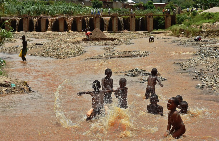 Children play in water in Bujumbura, on March 19, 2015. (AFP Photo/Carl Souzacarl de souza)