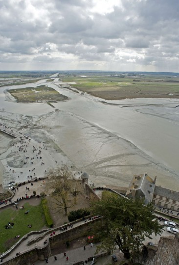"People wait for the wave named ""Mascaret"" in front of the Mont-Saint-Michel. Thousands of people flocked to Mont Saint-Michel, a Gothic Benedictine abbey perched on a rocky island, to watch what they hoped would be a ""tide of the century"" surround the picturesque landmark on France's northern coast. (Guillaume Souvant/AFP-Getty Images)"