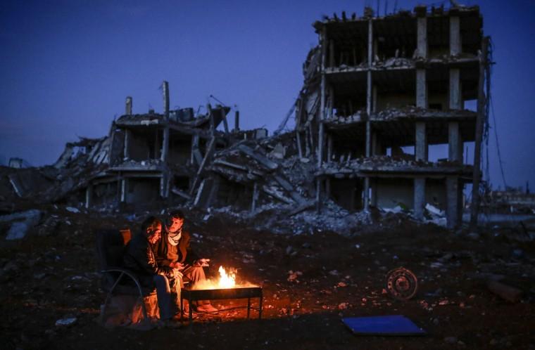 Kurdish men sit near bonfire near a destroyed building, in the Syrian Kurdish town of Kobane, also known as Ain al-Arab, on March 22, 2015. (AFP Photo/Yasin Akgul)