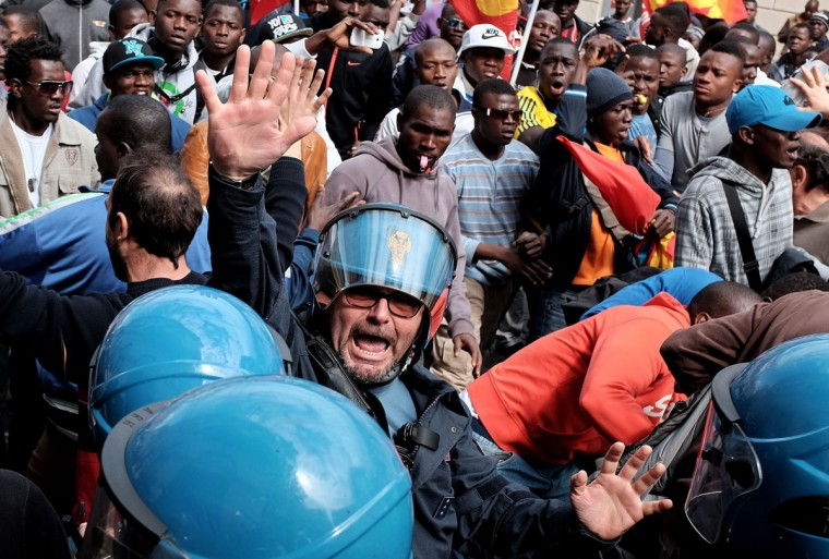 A Police officer gestures during a demonstration of asylum-seeking immigrants in Rome on March 23, 2015. (AFP Photo/Alberto Pizzoli)