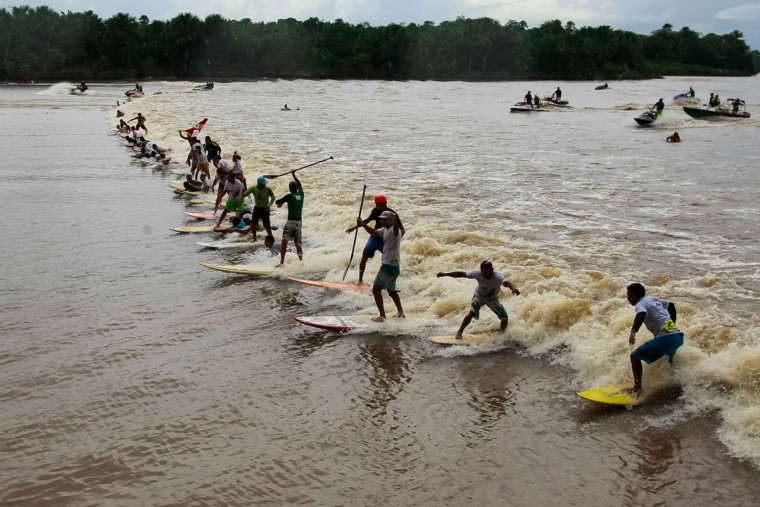 """People surf on the wave of a tidal bore known as """"Pororoca"""" during the annual surfing Pororoca festival in Sao Domingos do Capim. (TARSO SARRAF/AFP/Getty Images)"""