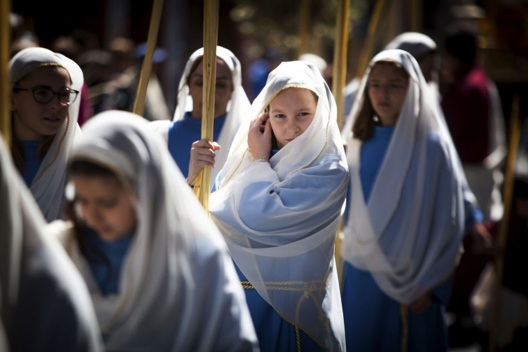 Girls hold palm leaves blessed during the morning Mass at the Cathedral of San Cristobal de La Laguna during a procession commemorating the arrival of Jesus in Jerusalem, on the Spanish Canary island of Tenerife on March 29, 2015. Palm Sunday held annually on the Sunday before easter and commemorates the entry into Jerusalem of Jesus Christ. (Desiree Martin/AFP/Getty Images)