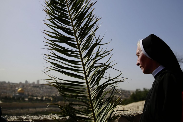 Catholic nun carries a palm branch during the traditional Palm Sunday procession from Mt. Olives to Jerusalem's Old City on May 29, 2015. The ceremony is a landmark in the Christian calendar, marking the triumphant return of Christ to Jerusalem the week before his death, when a cheering crowd greeted him waving palm leaves. Palm Sunday marks the start of the most solemn week in the Christian calendar. (Gali Tibbon/AFP/Getty Images)