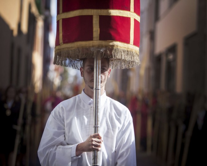 An altar boy carries a cross after the morning Mass at the Cathedral of San Cristobal de La Laguna during a procession commemorating the arrival of Jesus in Jerusalem, on the Spanish Canary island of Tenerife on March 29, 2015. Palm Sunday held annually on the Sunday before Easter and commemorates the entry into Jerusalem of Jesus Christ. (Desiree Martin/AFP/Getty Images)