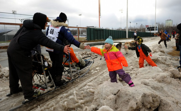 Musher Timothy Hunt, from Marquette, MI, gives a high five to Katelynn Ford and Anthony Ford at the bottom of Cordova Hill during the ceremonial start of the 2015 Iditarod Sled Dog Race in Anchorage, AK on Saturday March 7, 2015. (AP Photo/Alaska Dispatch News, Bob Hallinen)