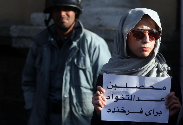 "An Afghan university student protests at the site where a mob beat to death a 27 year-old woman, Farkhunda, in Kabul, Afghanistan, Thursday, March 26, 2015. Farkhunda, who went by one name like many Afghans, was beaten, run over with a car and burned before her body was thrown into the Kabul River, last week. Persian on the poster reads, ""university students, justice for Farkhunda."" (AP Photo/Massoud Hossaini)"
