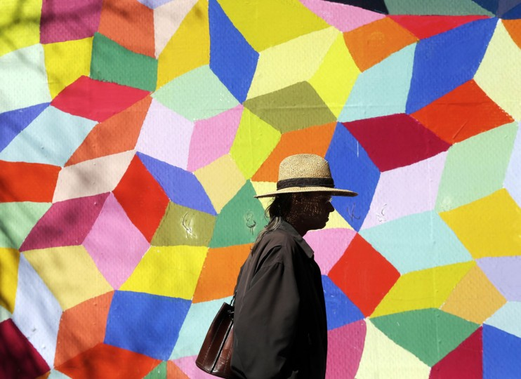 A man walks in front of a colorful mural along Market Street on Wednesday, March 4, 2015, in San Francisco. (AP Photo/Marcio Jose Sanchez)