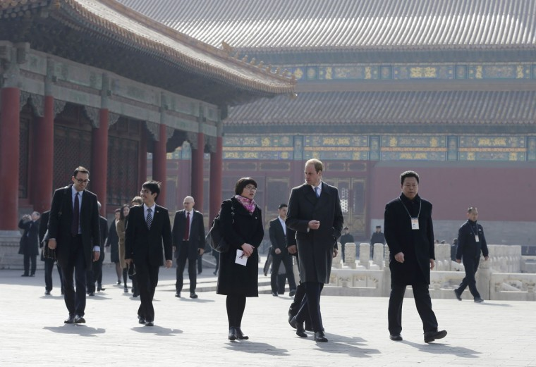 Britain's Prince William, second right in front, is guided by Chinese officials as he tours the Forbidden City in Beijing Monday, March 2, 2015. William presented China's president with a large envelope Monday containing an invitation from the queen to visit Britain this year, as he began the first official visit to mainland China by a senior British royal in a generation. (AP Photo/Andy Wong, Pool)