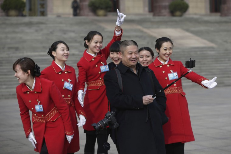 Chinese hostesses who serve the delegates of the National People's Congress share a light moment as they pose for a selfie photo with a photographer during a plenary session of the NPC held at the Great Hall of the People in Beijing Thursday, March 12, 2015. Thousands of delegates from across the country are in the Chinese capital to attend the annual National People's Congress and the Chinese People's Political Consultative Conference. (AP Photo/Andy Wong)