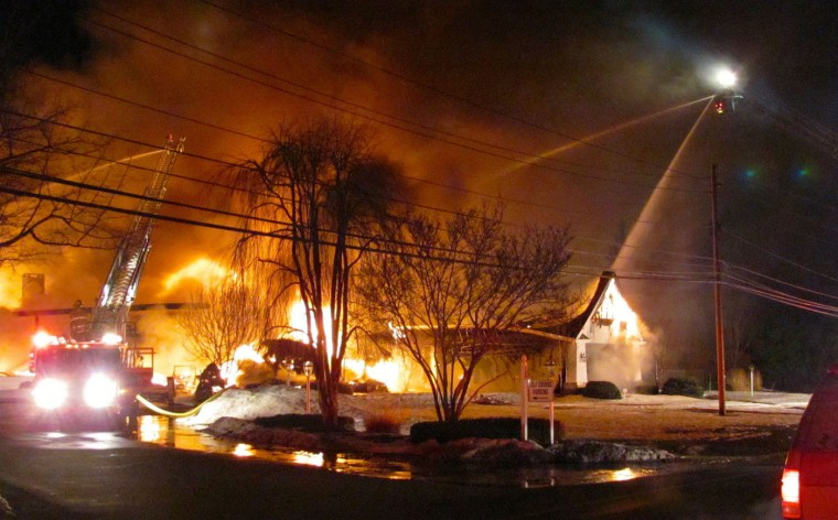 Firefighters try to put out a fire at the main clubhouse of the Madison Country Club Thursday morning, March 12, 2015, in Madison, Ohio. Fire officials say crews from more than 20 departments and three counties were called to help fight the flames. Officials say the fire spread quickly and the building is considered to be a complete loss. (AP Photo/The Plain Dealer, Cliff Pinckard)