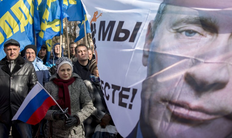 A poster stands near to a banner with the image of Russian President Vladimir Putin, during a rally marking the one year anniversary of the referendum in Crimea that supported its secession from Ukraine, in Simferopol, Crimea, Monday, March 16, 2015. (AP Photo/Mikhail Mordasov)