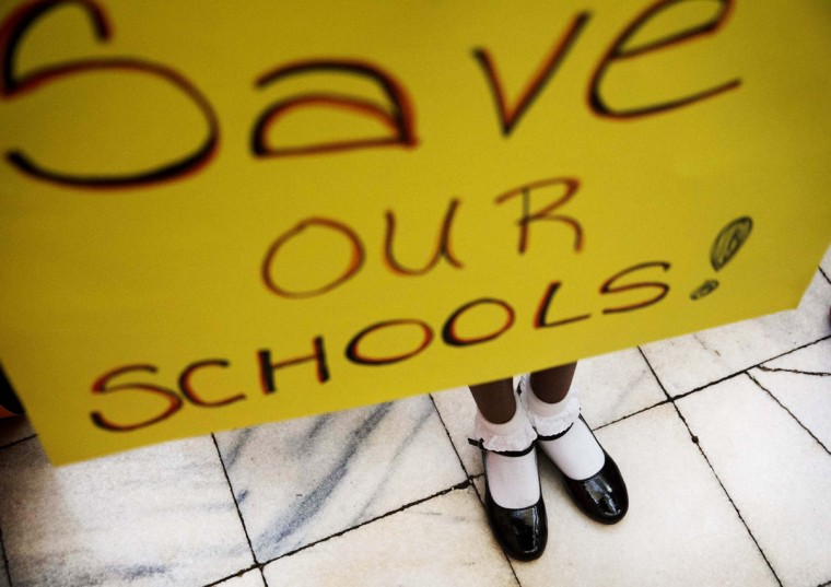 "The shoes of Browns Mill Elementary School fourth-grader Sydney Robinson peek out from under a sign she holds during a rally against Georgia Gov. Nathan Deal's proposal to take over schools dubbed ""chronically failing"" at the Capitol, Monday, March 23, 2015, in Atlanta. A key House committee is expected to vote on Gov. Deal's proposal Monday afternoon. The Senate already has passed the constitutional amendment and accompanying legislation but the Republican governor could face a tougher fight in the House. (AP Photo/David Goldman)"