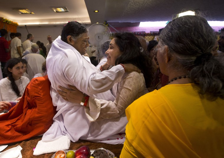"Indian spiritual leader Mata Amritanandamayi, center left, hugs to bless a devotee during a prayer meeting in New Delhi, India, Monday, March 30, 2015. Known among her followers as ""Amma,"" which means ìmother"" in several Indian languages, Amritanandamayi has devotees in India and the rest of the world. She is also popularly known as the Hugging Saint.(AP Photo/Saurabh Das)"